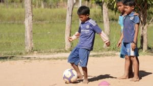 boy doing football drills while two others wait