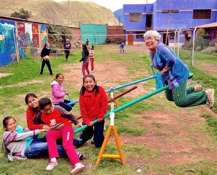 Volunteer playing with children on the playground at Picaflor House