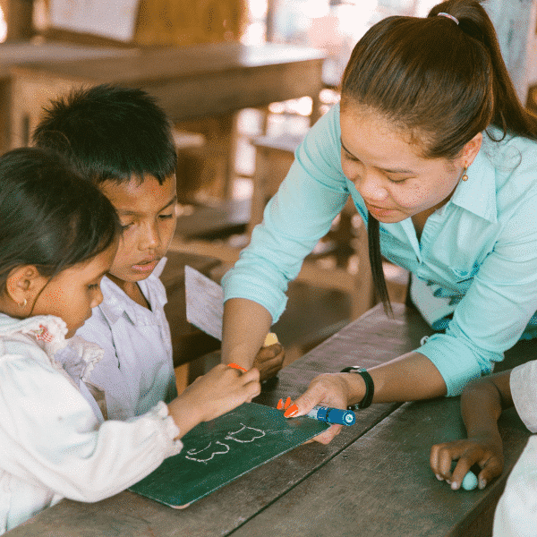 Cambodian teacher helping the kids