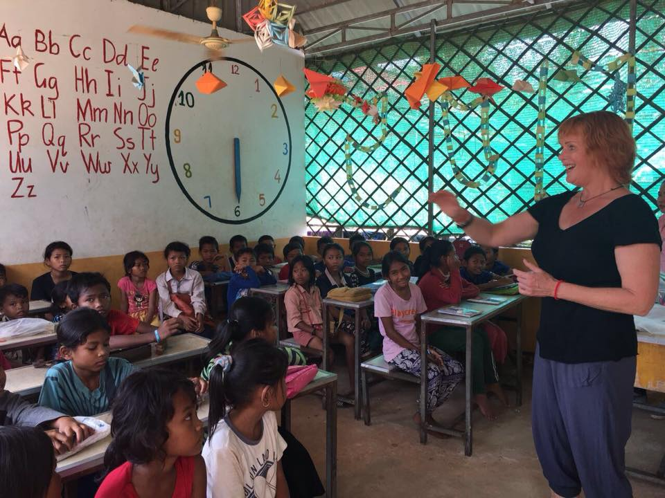 volunteer hands out tooth brushes in Cambodia
