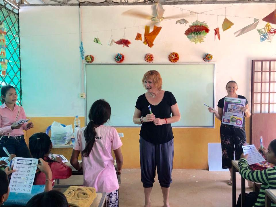 Volunteer in cambodia hands out toothbrushes