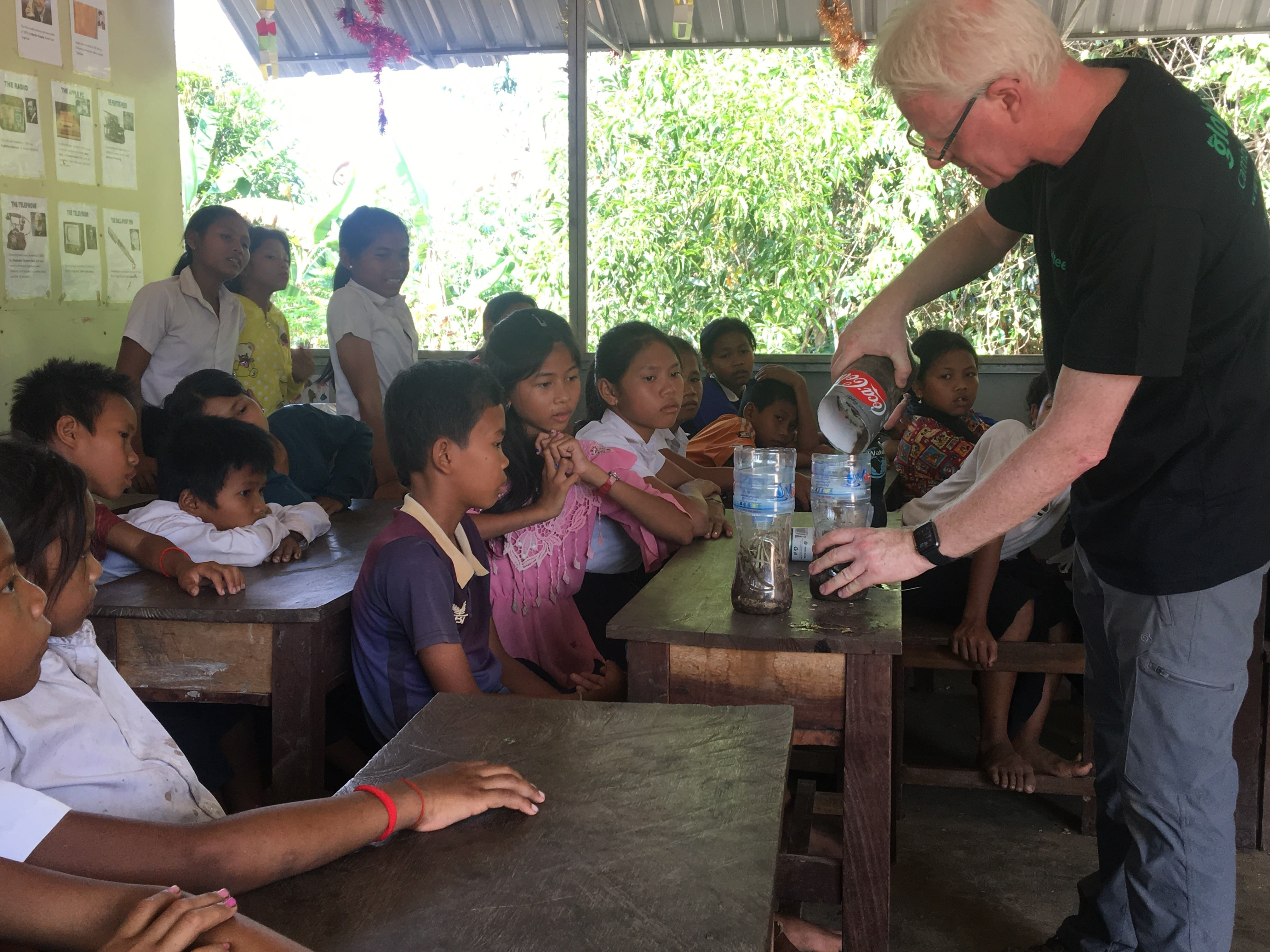 Volunteer showing children how to compost in Cambodia