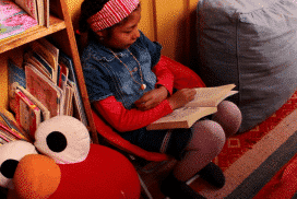 Student reading at free library project for kids in Peru