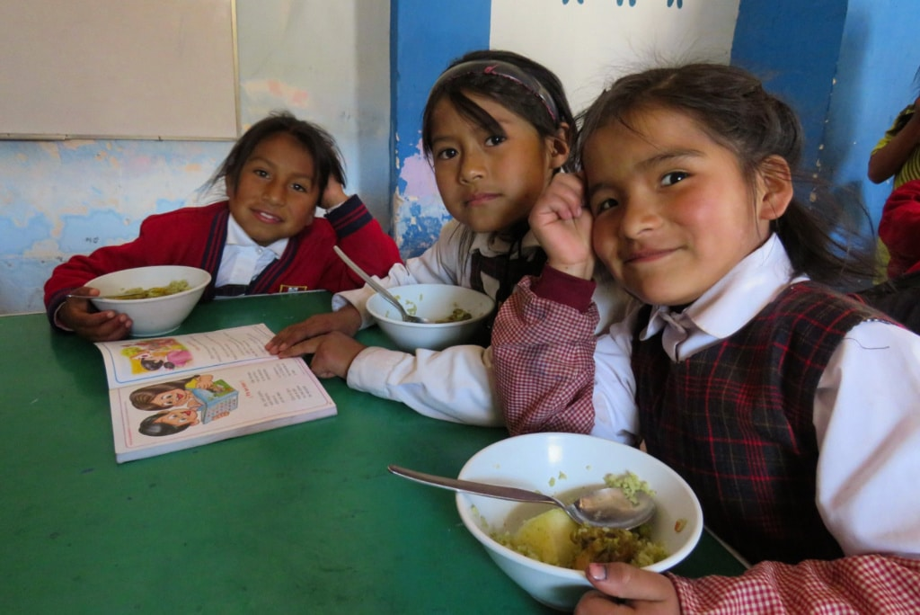 three girls eating lunch at our Peru education project